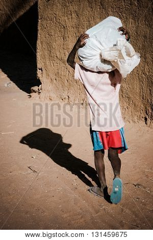 Young african boy carrying a bag on the head, back view