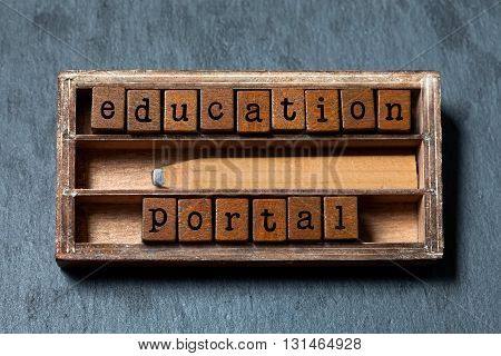 Education portal conceptual image. Vintage blocks with text, retro style pencil in wooden box. Gray stone background, macro