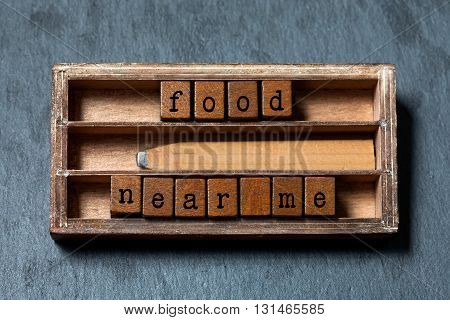Food near me. conceptual text. Wooden boxes with letters, retro pencil, aged box background. Gray stone, macro