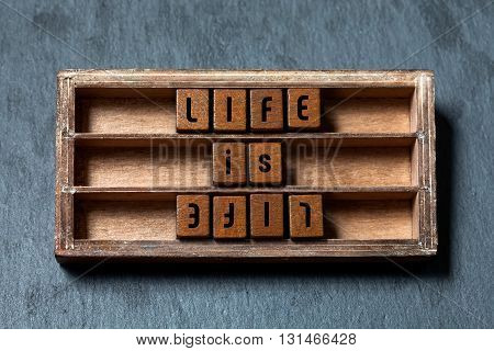 Life is life, opposite opponent concept. Shabby wooden box, cubes with old style letters, Gray stone textured background. Close-up, up view
