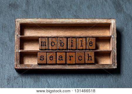 Mobile search concept text. Wooden shelf with textured blocks and letters. Gray stone background, macro, soft focus.