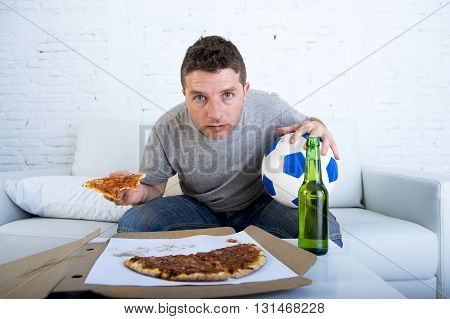 young man alone holding ball and beer bottle in stress watching football game on television at home living room sofa couch with pizza box excited and in disbelief face expression