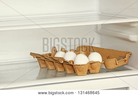 Fresh eggs in a paper box on refrigerator shelf taken closeup.