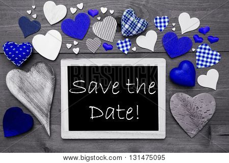 Chalkboard With English Text Save The Date. Many Blue Textile Hearts. Grey Wooden Background With Vintage, Rustic Or Retro Style. Black And White Style With Colored Hot Spots