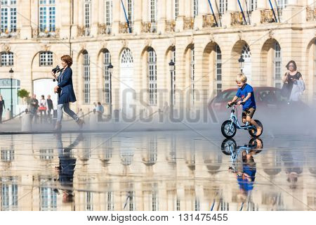 People Having Fun In A Mirror Fountain In Bordeaux, France