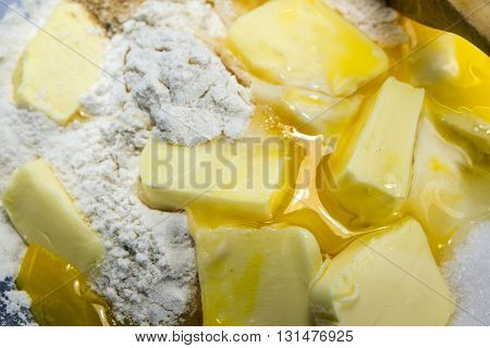 flour eggs butter and sugar ingredients for shortcrust pastry baking background closeup as a baking background with selected focus an narrow depth of field