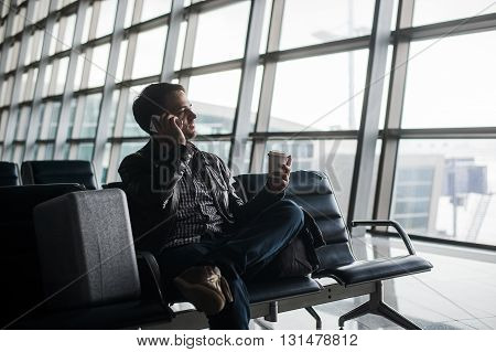 Portrait of young handsome man wearing casual style clothes sitting on the bench in modern airport using smartphone. Passenger travelling with luggage bag making call, while waiting for his flight.