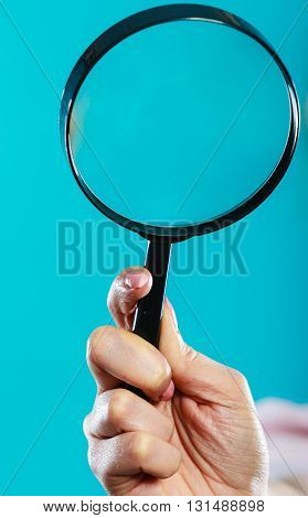 Investigation exploration education concept. Closeup woman holding magnifying glass loupe in hand on blue background