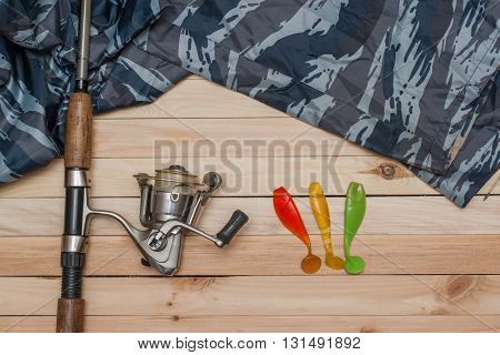 Set for fishing on the wooden background with camouflage clothing. Coil colored rubber bait spinning fishing rod. Fishing and recreation.