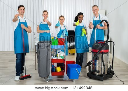 Group Of Happy Cleaners Standing With Cleaning Equipments In Office poster