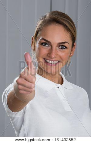 Portrait Of Young Woman Showing Thumbs Up Sign