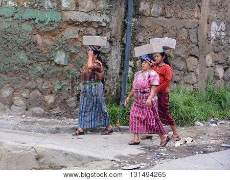 SANTA CATARINA PALOPO DE ATITLAN GUATEMALA NAY 01 2016: Maya women carring concrete block on their head. he Mayan people still make up a majority of the population in Guatemala