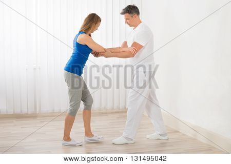 Physiotherapist Assisting Happy Mature Woman For Exercising