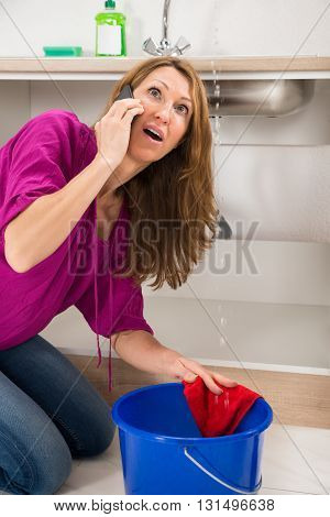 Angry Woman Calling To Plumber While Leakage Water Falling Into Bucket