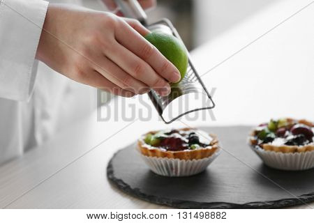Female hands decorating fruit tarts with lime zest