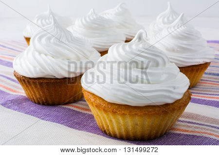 White cupcakes on the linen napkin. Sweet pastry. Sweet dessert. Birthday cupcakes. Homemade cupcake. Sweet cupcake. Gourmet cupcakes.