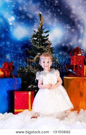 Christmas child standing in snowdrift against night stellar sky.