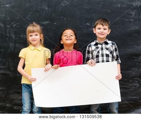 three cute children holding an empty paper sheet for ad with chalky blackboard on background