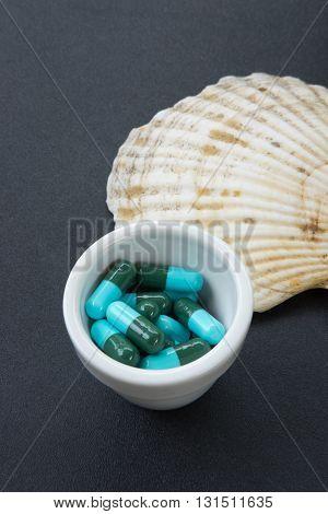 heap of blue green round capsule on black wood