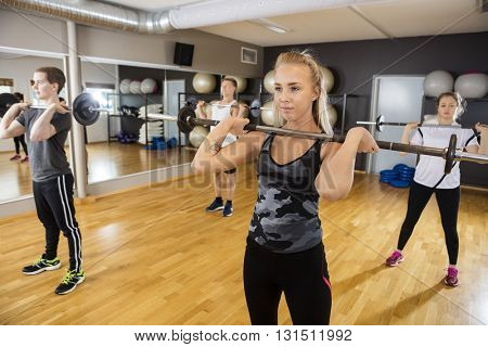 Friends Lifting Barbells While Standing In Health Club