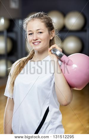 Attractive Woman Smiling While Lifting Kettlebell In Gym