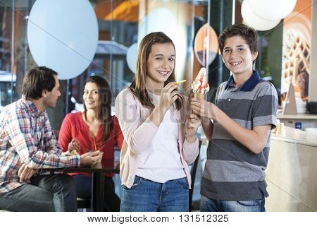 Smiling Brother And Sister Having Vanilla Ice Cream In Parlor
