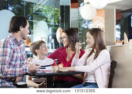 Loving Family Having Ice Creams At Table In Parlor