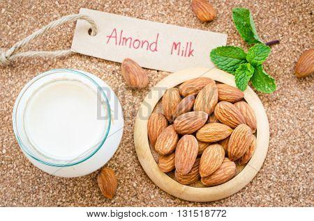 Almond milk organic healthy nut vegan vegetarian drink with almond milk tag on wood background.