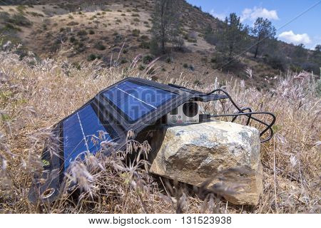 LAKE ISABELLA USA - MAY 24 2016: When hiking or living off the grid a folding solar charger is a convenient way to keep small cameras and other devices powered up.