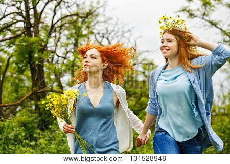 Best friends forever. Girlfriends have fun and carefree walk in the park. BFF. A girl holding a bouquet of wildflowers. A wreath of flowers at the girl on the head.