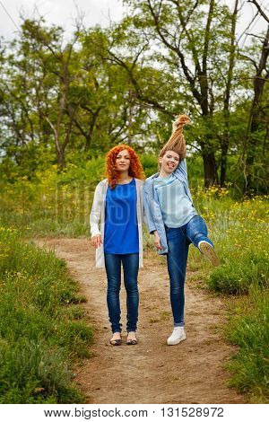 Best friends forever. Girlfriends standing on a footpath in the park. BFF. Close friends. Gentle friendship. Girl holding her hair