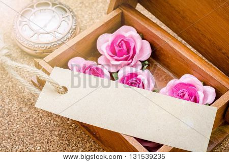 Black card and pink rose with vintage pocket watch on wood background Ready for your text or message.