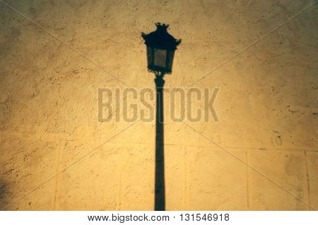 Streetlight shadow on a yellow wall in Meknes, Morocco, Africa