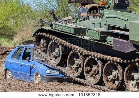 a heavy military tank crushes a blue car