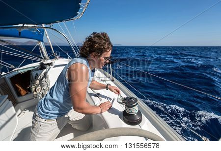 Young man on yacht working with winch
