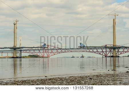 SOUTH QUEENSFERRY SCOTLAND UK - MAY 15 2016: Construction of central and southern towers of The Queensferry Crossing a new road bridge built close to the Forth Road Bridge and Forth Bridge spanning the River Forth in Scotland.