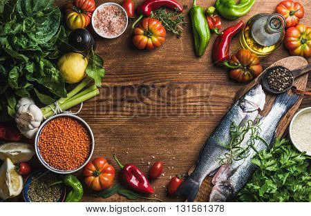 Ingredients for cooking healthy dinner. Raw uncooked seabass fish with vegetables, grains, herbs and spices over rustic wooden background. Copy space, top view