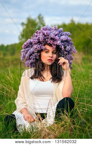 Young beautiful girl in a lilac wreath sitting in a field.