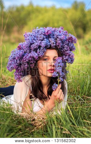 Young beautiful girl in a lilac wreath lying at field.