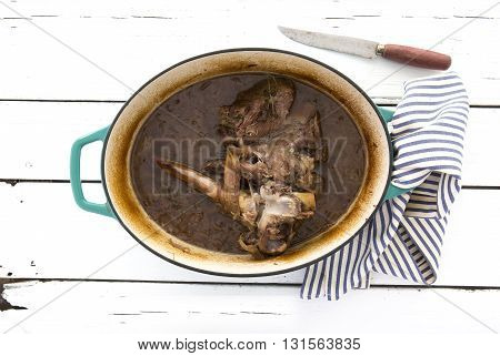 Slow cooked lamb with onions and red wine on old wooden table