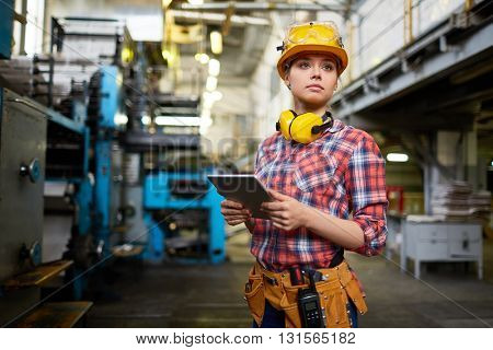 Pretty female student doing practical work at factory