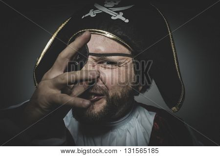 Derision. man pirate with eye patch and old hat with funny faces and expressive poster