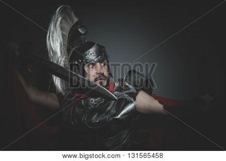 Historic, Praetorian Roman legionary and red cloak, armor and sword in war attitude