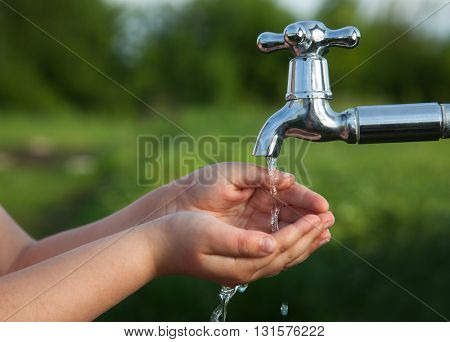 boy washes his hand under the faucet in the garden