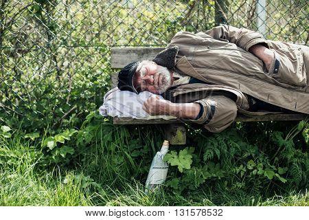 Homeless Man Sleeping On Bench In Park.