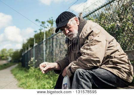 Homeless Man On Bench In Park Smoking Cigarette.
