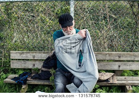 Homeless Man On Outdoors Bench Pulling Sweater.