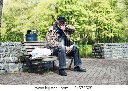 Homeless Man Wipes His Mouth With His Sleeve.