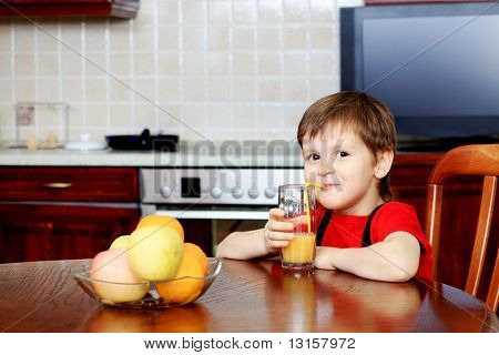Little boy is drinking a juice at home.