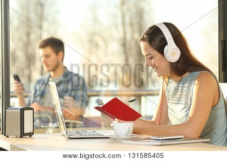 Profile of female listening music with headphones working on line writing notes in agenda in a coffee shop with people outside in the background